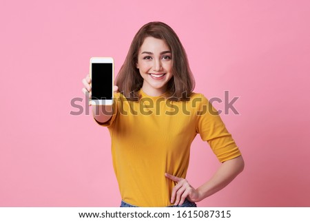Portrait of happy young woman showing at blank screen mobile phone isolated over pink background. #1615087315