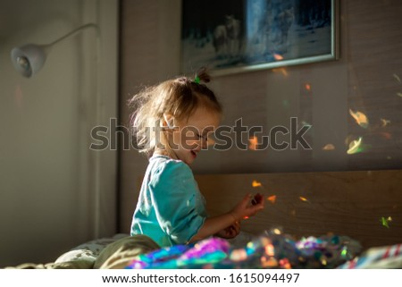 Little cute laughing girl in blue pajamas playing with sunlight spots made with a sparkling dress in bedroom on a sunny morning. #1615094497