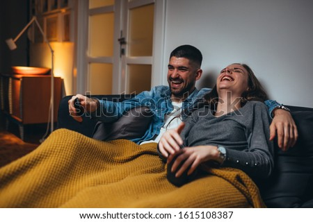 romantic couple laying sofa in their living room watching movie on television #1615108387