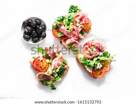 Bruschetta with prosciutto, ciabatta bread, romano salad, tomatoes, cream cheese and sun dried olives on a light background, top view #1615132792