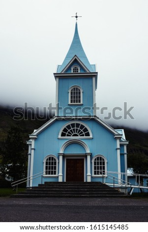 A Little Blue Church Stands Out On A Low Overcast Day #1615145485