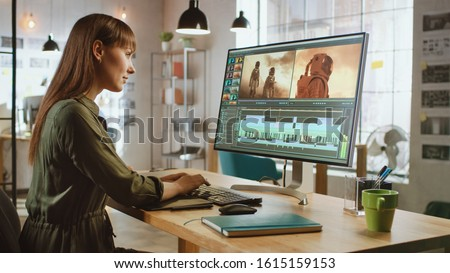 Beautiful and Creative Brunette Female Video Editor Works with Footage on Her Personal Computer with Big Display. She Works in a Cool Office Loft. Royalty-Free Stock Photo #1615159153