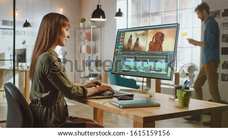 Beautiful Brunette Female Video Editor Works with Footage on Her Personal Computer with Big Display. She Works in a Cool Office Loft. Other Male Creative Colleague Walks in the Background. #1615159156