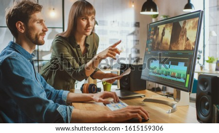 Beautiful Female Art Director Consults Handsome Video Editor Colleague, They Work on a Video Project About Astronauts. They Work in a Cool Office Loft. They Look Very Creative and Cool. #1615159306