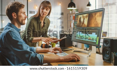 Beautiful Female Art Director Consults Handsome Video Editor Colleague, They Work on a Video Project About Astronauts. They Work in a Cool Office Loft. They Look Very Creative and Cool. #1615159309