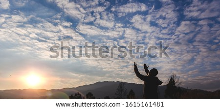 Man lift hands praying at sunset on mountain. christian concept.