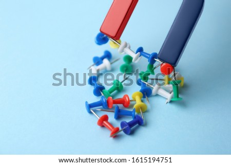 Magnet attracting colorful pins on light blue background, closeup #1615194751