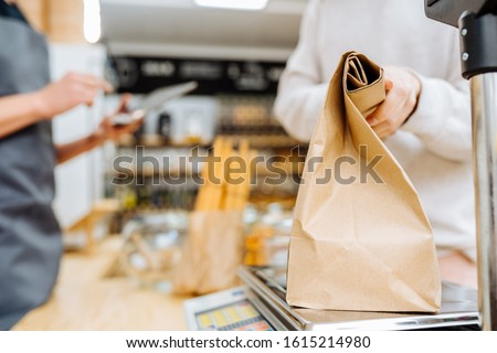 Woman chooses and buys products in zero waste shop. Weighing dry goods in plastic free grocery store. Unrecognizable girl paper bag on scales. Eco shopping at local business #1615214980