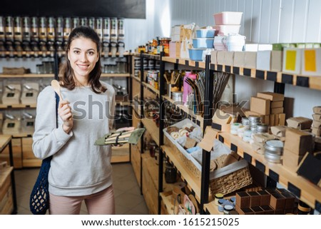 Eco friendly vegan woman customer chooses and buys products in zero waste shop. Eco shopping at local business concept. Plastic free items. reuse, reduce #1615215025