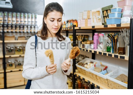 Eco friendly vegan woman customer chooses natural coconut soap and brushes for washing dishes, and buys products in zero waste shop. Eco shopping at local business concept. #1615215034