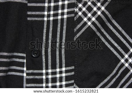 Button on black checkered shirt. Close up of simple button on casual plaid women shirt, casual black and white pattern blouse  #1615232821