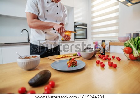 Cropped picture of handsome dedicated caucasian chef in uniform standing in kitchen and cutting orange for decoration. On kitchen counter are vegetables and prepared delicious dish.