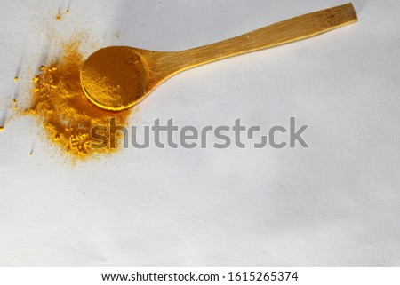 Yellow curry and yellow spoon at white background. Kitchen spices. Spicy food. Organic flavour. Isolated image. Color powder. Wooden spoon with curry. Closeup picture. Natural food. Cooking in India