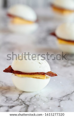 Keto BLT egg sandwich, or egg bun snack for the ketogenic diet plan. Boiled eggs with turkey bacon and cheddar cheese. Selective focus with blurred background.