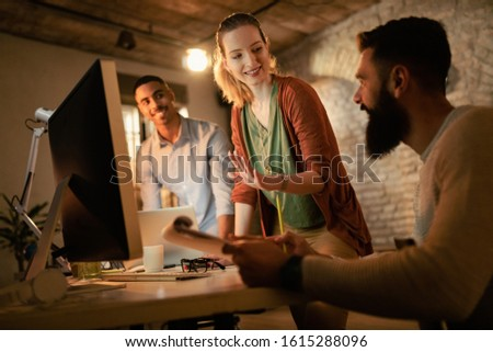 Young smiling businesswoman and her coworkers communicating while working on desktop PC in the office.  #1615288096
