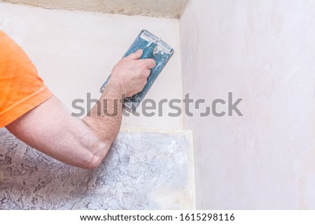 Plasterer smooths the walls with sandpaper close-up. Male hand of a worker. Stock photo. #1615298116
