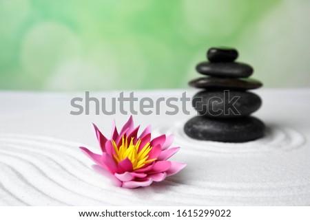 Zen garden. Beautiful lotus flower and stones on white sand #1615299022