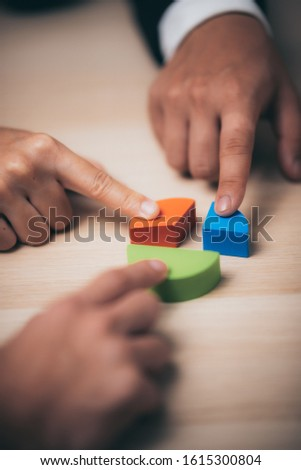 businessman hand placing the last jigsaw puzzle piece, Hand holding missing jigsaw puzzle piece down in to the place, conceptual of problem solving, finding a solution. #1615300804