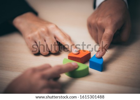 businessman hand placing the last jigsaw puzzle piece, Hand holding missing jigsaw puzzle piece down in to the place, conceptual of problem solving, finding a solution. #1615301488