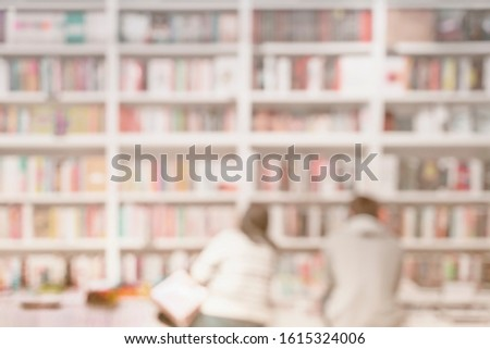 Abstract blurred unrecognizable woman and man in bookstore, bookshelves with books on bookshelves in library or in book store, soft focus. Concept of learning, school, culture, education #1615324006