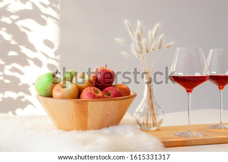 Two burgundy glasses of red wine, wooden bowl with green and red apples, decor vase on table in kitchen on white background. Copyspace. Place for text, interior catalog, wine degustation #1615331317