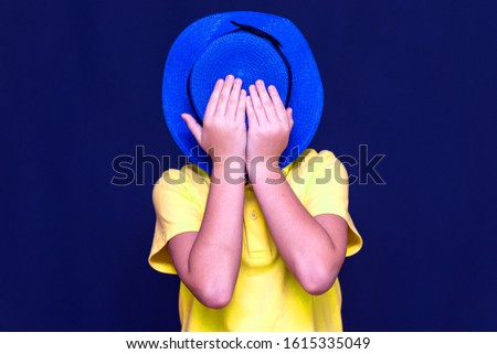 Portrait of happy joyful caucasian boy  on blue studio background.Boy with blue hat. face hidden with a hat.Toned picture.
