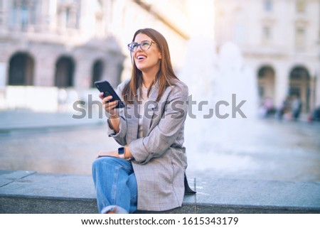 Young beautiful woman smiling happy and confident. Sitting with smile on face using smartphone at the city #1615343179