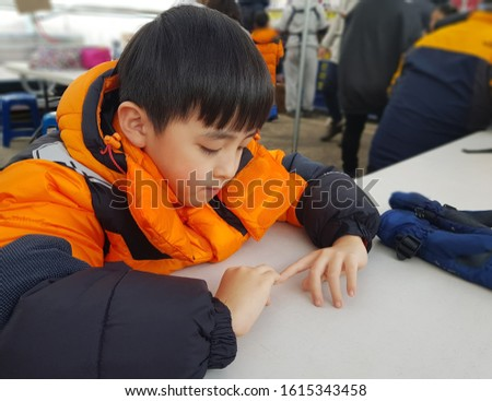 A boy in an orange jacket is looking at his finger with his hands on the table. Out Focus picture.