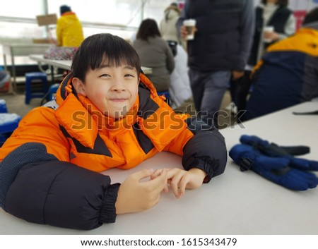 A boy in an orange jacket is smiling, looking straight ahead, with his hands on the dining table. Out Focus picture.