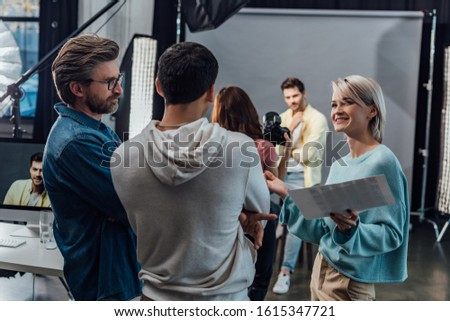 selective focus of happy woman looking at coworker near art director in photo studio #1615347721