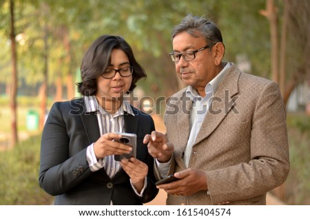 Young Indian woman manager/entrepreneur in western formals or suit with old Indian man teaching him how to operate a mobile phone promoting digital literacy for elderly in a park in New Delhi, India #1615404574