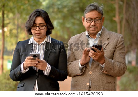 Young Indian woman manager/entrepreneur in western formals or suit with old Indian man. Both working on their own mobile promoting digital literacy for elderly in a park in New Delhi, India #1615420093