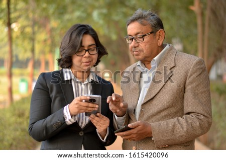 Young Indian woman manager/entrepreneur in western formals or suit with old Indian man. Both working on their own mobile promoting digital literacy for elderly in a park in New Delhi, India #1615420096