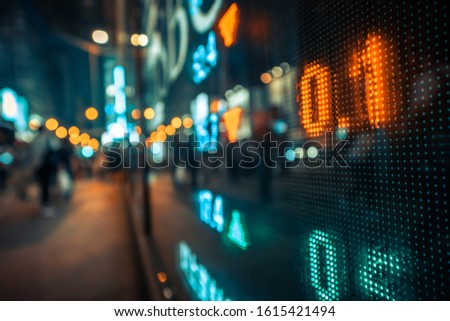 Display stock market numbers and graph with city light reflections at the street. Small focus line, some noise. Blurry. #1615421494
