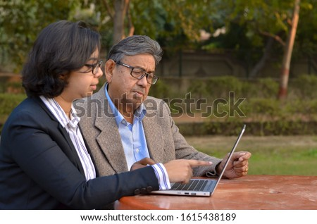 Young Indian woman manager/entrepreneur in western formals or suit helping old Indian man on a laptop promoting digital literacy for elderly in a park in New Delhi, India #1615438189