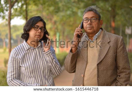 Young Indian woman manager/entrepreneur in western formals or suit with old Indian man. Both speaking on their own mobile phone promoting digital literacy for elderly in a park in New Delhi, India #1615446718