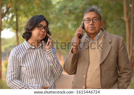 Young Indian woman manager/entrepreneur in western formals or suit with old Indian man. Both speaking on their own mobile phone promoting digital literacy for elderly in a park in New Delhi, India #1615446724