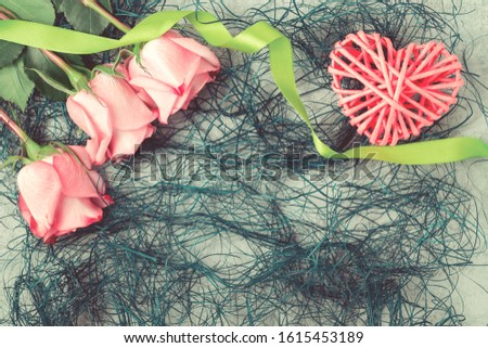 Flower arrangement - bouquet of pink roses and wicker heart on concrete surface, template for design or greeting card, place for text, copy space