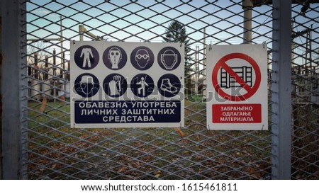 """Couple of warning signs. One says """"Use protective suit"""" and other is saying """"Forbidden to store items"""". Written in Serbian language. #1615461811"""