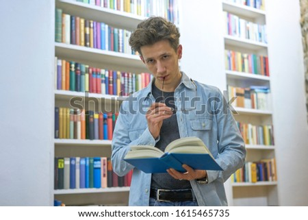 Young, seriously looking man, standing in library with glasses on his mouth, lost in thought. #1615465735