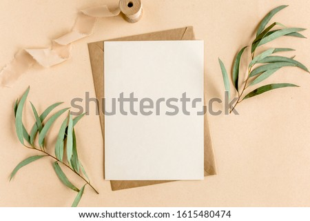 Mockup invitation, blank greeting card and green leaves eucalyptus. Flat lay, top view. Royalty-Free Stock Photo #1615480474