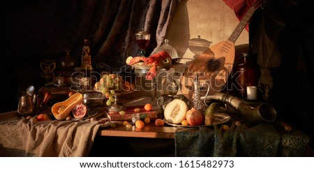 Still life in old masters style with lobster, glass of wine, silver dishes, fruits, guitar lute and hunting horn.             Royalty-Free Stock Photo #1615482973