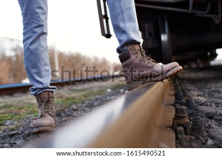 Girl in boots walks through the railroad tracks in autumn #1615490521
