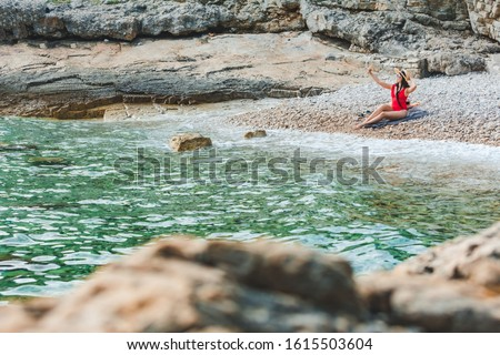 young pretty woman in red swimsuit sitting at rocky beach with phone taking selfie picture