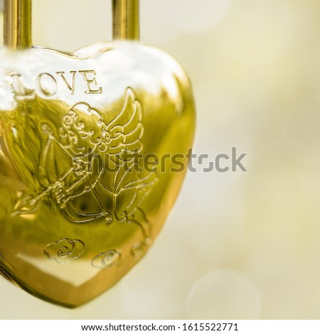 Hinged gold lock in the form of a heart, the inscription love angel with an arrow on a blurred background. Symbol of wedding. #1615522771