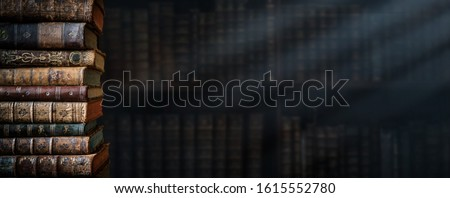 Old books on wooden shelf and ray of light. Bookshelf history theme grunge background. Concept on the theme of history, nostalgia, old age. Retro style. #1615552780