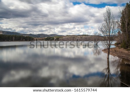 Landscape of trees in calm lake water with white clouds sky reflected and mountains in background #1615579744