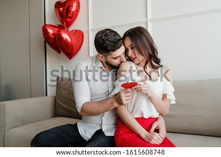 handsome couple man and woman with valentine card and heart shaped balloons on couch at home #1615608748