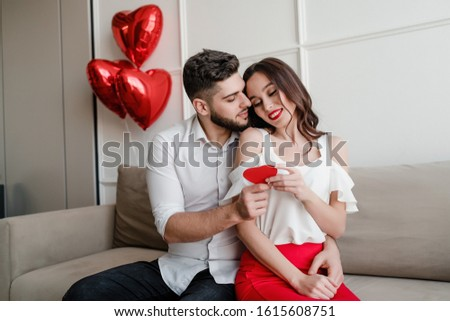 handsome couple man and woman with valentine card and heart shaped balloons on couch at home #1615608751