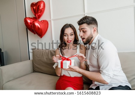 wife unpacking present in gift box from husband sitting on sofa in apartment #1615608823